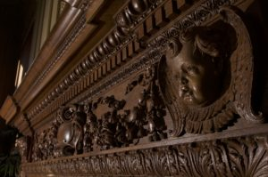 Detail of the carved wood fireplace mantel of Holmes Lounge.