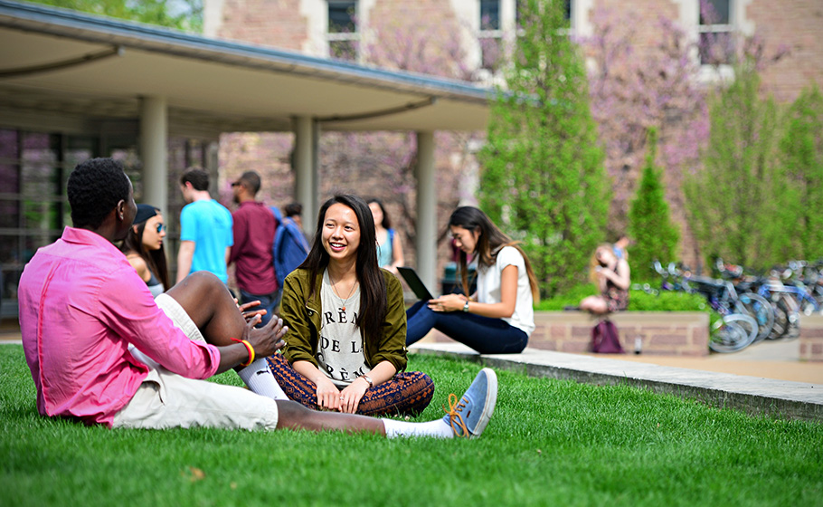 students sitting on grass by Olin library