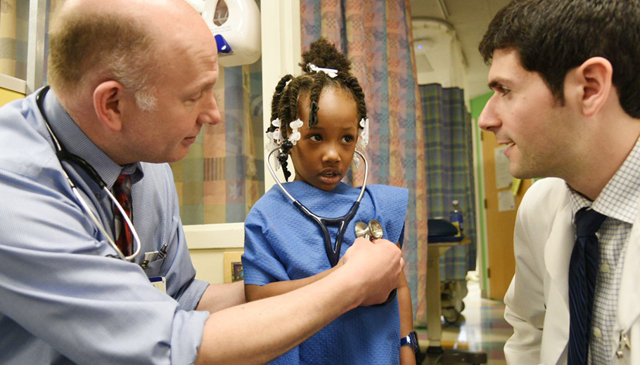 third-year medical student, Ari Berlin and faculty member, Andrew White consult african-american girl patient