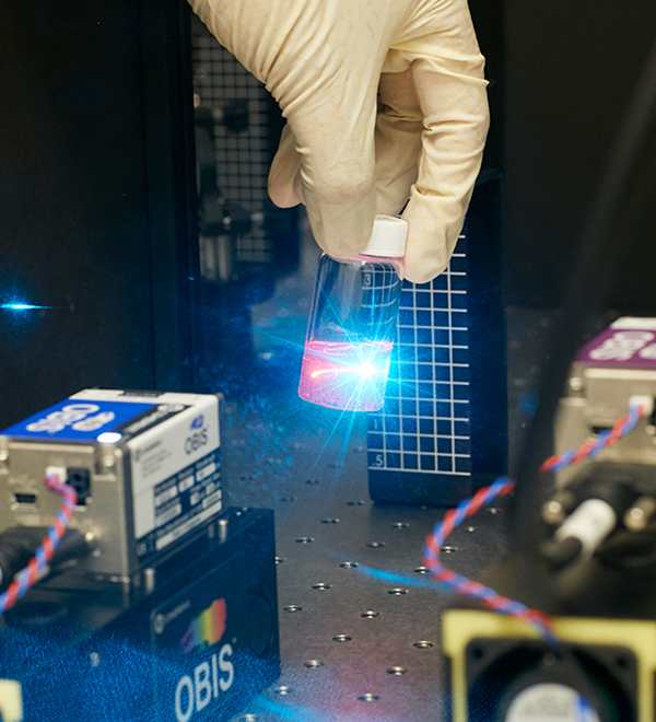 A teal laser causes fluorescent molecules to glow pink
