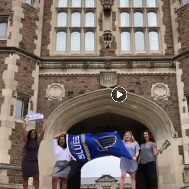 Students dancing with a St. Louis Blues flag in front of Brookings Hall