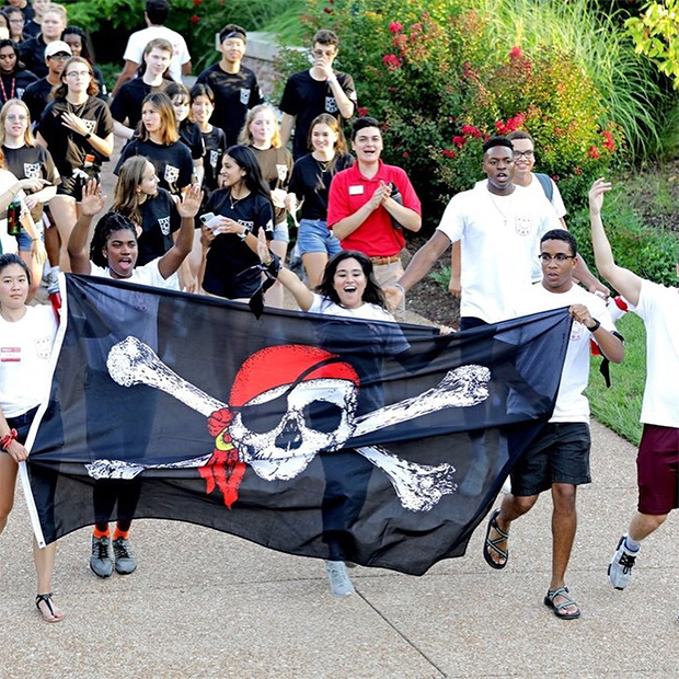 Students in matching T-shirts walk in a group while holding a black flag with skull and crossbones