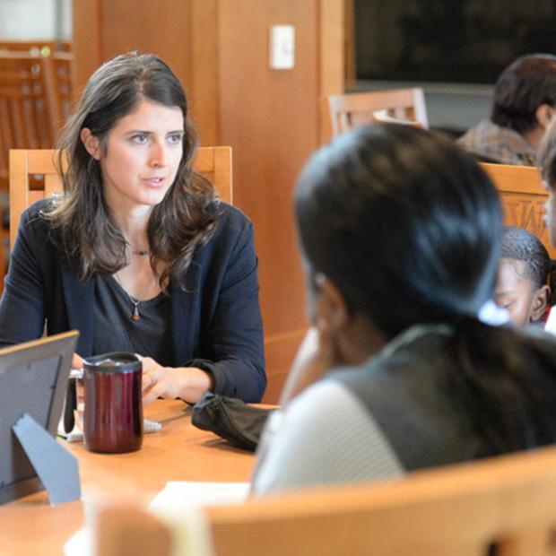 Women in business attire speak with each other