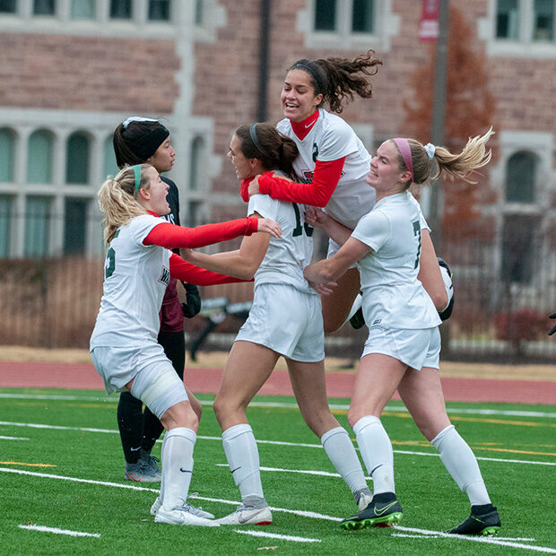 Members of WashU women's soccer team leap together for a group hug