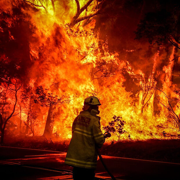 Firefighter stands in front of flames