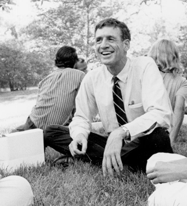 Black and white photo of William H. Danforth sitting on the ground with students