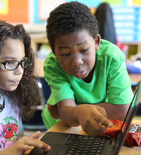 Two elementary school students work on a laptop