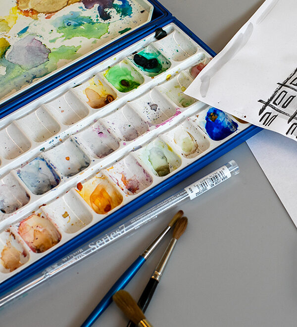 tabletop of a watercolor palette and brushes
