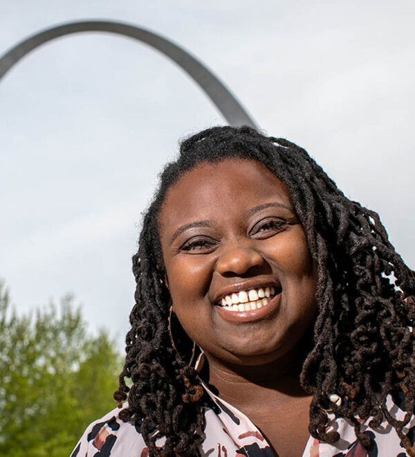 WashU 2021 graduate, Chelsea Carter stands with the St. Louis Arch in the background