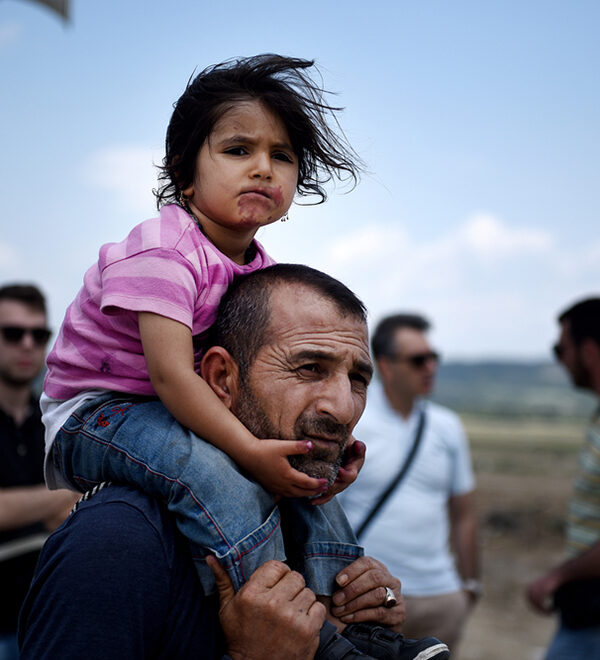 A refugee man with his daughter on his shoulders