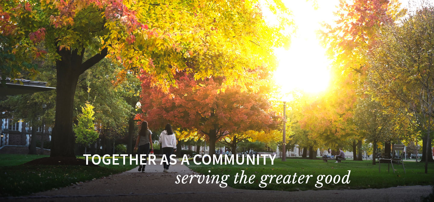 Two people walk across campus with sunlight shining through fall foliage. Together as a community, serving the greater good.